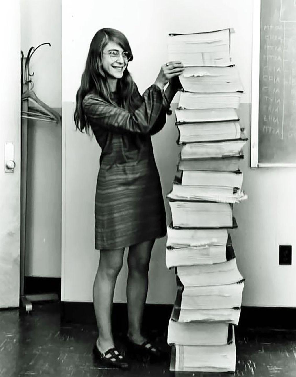 Hình ảnh bên dưới chụp nữ kĩ sư trưởng Margaret Hamilton của dự án đứng bên chồng giấy in những đoạn code của Apollo 11